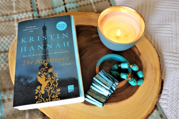 The book is The Nightingale by Kristen Hannah placed on a wooden board with an accessory of a candle and some bracelets